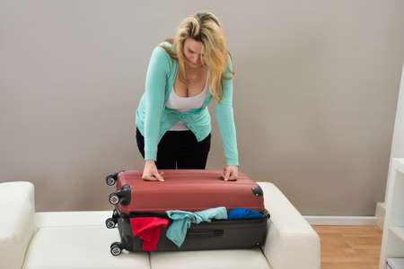 overfilled: Woman Trying To Close The Overfilled Suitcase In The Room