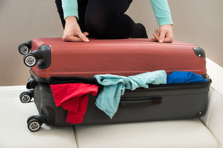 overfilled: Close-up Of Woman Trying To Close Suitcase With Excess Of Clothes