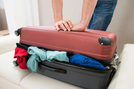 overfilled: Close-up Of Person Hand Trying To Close Suitcase On Sofa