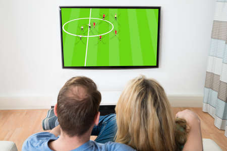 Couple Watching Sports On Television At Home photo