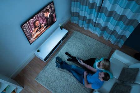 Vista elevada de pareja viendo la película en la sala de estar