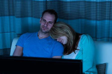 mujer viendo tv: Pareja sentada en el sofá que ve la televisión en casa