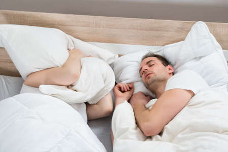 pareja durmiendo: Esposa tapando las orejas De Cojín Mientras marido ronquido en dormitorio