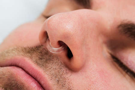 snoring: Extreme Close-up Of Man Face With Nose Clip Device