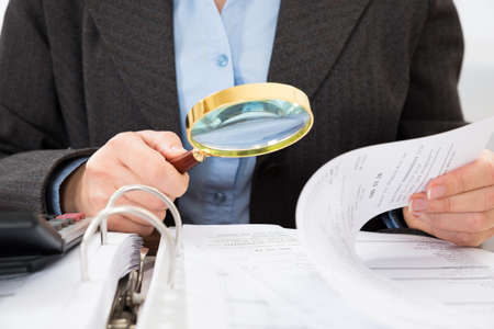 auditoría: Primer plano de hombre de negocios que controla cuentas con la lupa