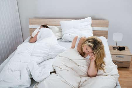 man and woman sex: Несчастная женщина с одеяло на кровати, а спящего в спальне