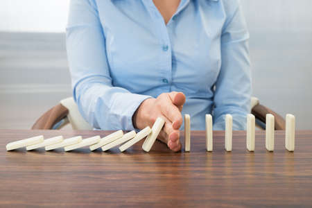 Close-up van zakenvrouw stoppen Het effect van Domino Met Hand Bij Bureau Stockfoto