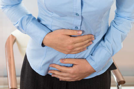 menopause: Close-up Of Businesswoman Suffering Stomachache In Office Stock Photo