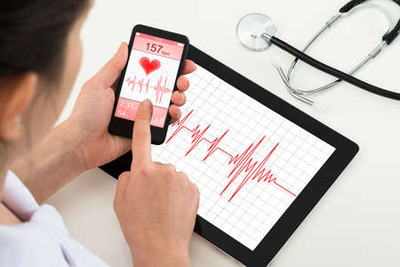 mobile devices: Close-up Of Doctor Holding Mobile Phone With App For Health Stock Photo