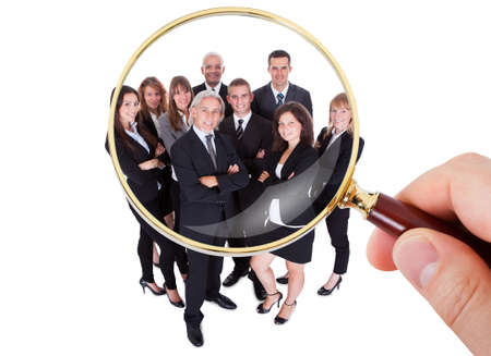 select: Person Hand Looking At Group Of Executives Through Magnifying Glass Stock Photo