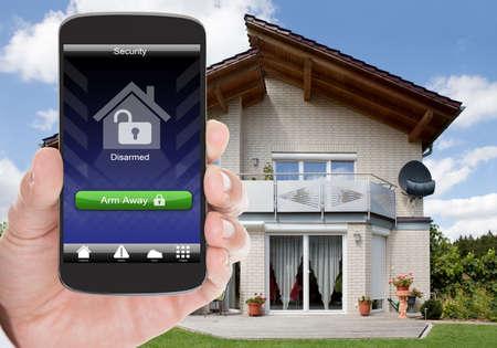 ホーム セキュリティ システムと携帯電話を保持している人の手のクローズ アップ