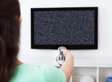 Close-up Of Woman Holding Remote Control In Front Of Television With No Signal Фото со стока