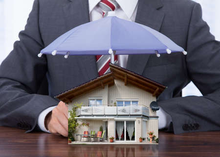 Businessman Providing Umbrella To House Model At Desk