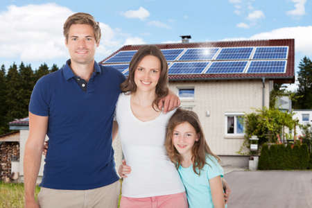 residential house: Family Standing In Front House With Solar Panel On Roof