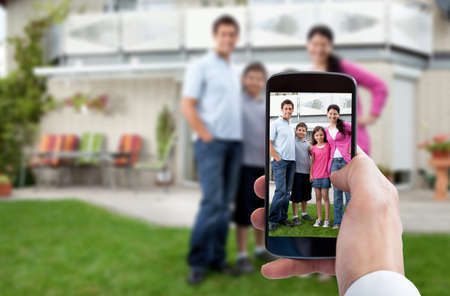 father and son holding hands: Person Hand Using Mobile Phone For Taking Family Photo