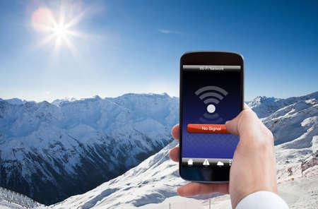 雪に覆われた山での携帯電話の Wifi 信号がないと人の手のクローズ アップ