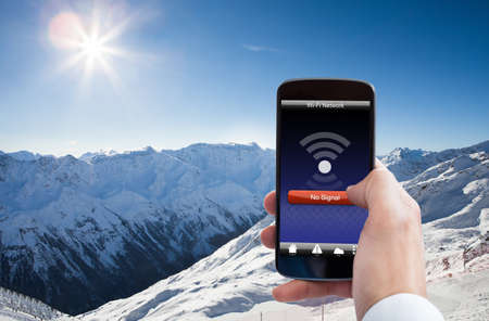Close-up Of Person Hand With No Wifi Signal On Mobile Phone In Snowy Mountain