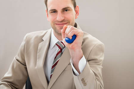 office physical pressure paper: Businessman Squeezing Blue Stress Ball At Desk