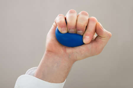 stress ball: Close-up Of Businessperson Hand Squeezing Stressball In Hand
