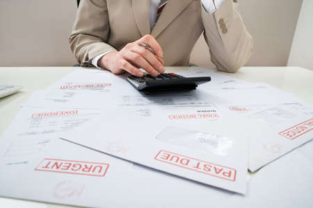 unpaid: Close-up Of Businessman Calculating With Calculator Unpaid Bills