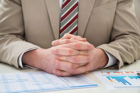gantt: Close-up Of Businessman With Hands Clasped Over Gantt Chart