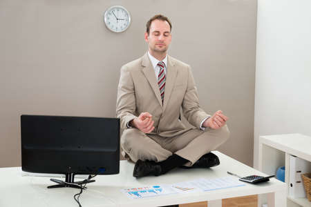 meditating: Businessman Sitting On The Desk And Meditating With Eyes Closed Stock Photo