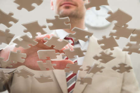 randomness: Businessman Separating Jigsaw Puzzle On Glass Table