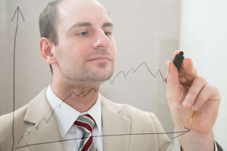 glass panel: Businessman Drawing A Graph On A Glass Panel With Marker Pen Stock Photo