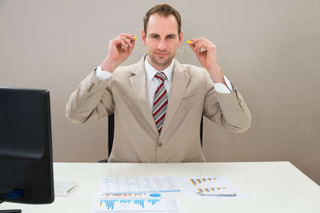 noise: Businessman Inserting Earplug In Ears At Desk In Office Stock Photo