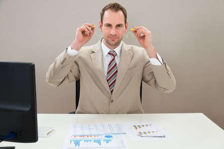 contaminacion acustica: Empresario Inserción auricular En Oídos En El Escritorio De Oficina Foto de archivo