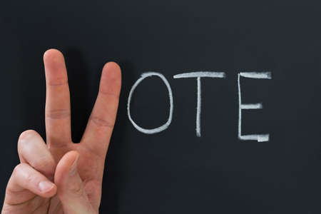 Close-up Of Finger Making V Sign With The Word Vote On Chalkboard
