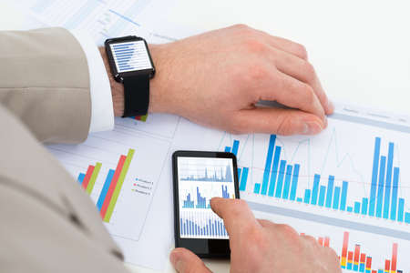 analyzing: Close-up Of Businessman Analyzing Graph With Mobile Phone And Smartwatch Stock Photo