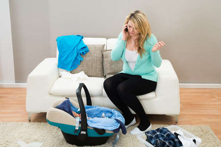 mums: Woman Talking On Mobile Phone With Laundry Clothes In Living Room