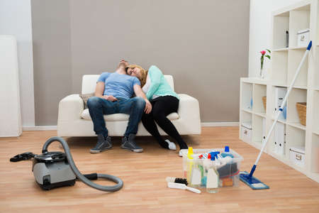 two couples: Exhausted Couple Resting On Sofa In Living Room
