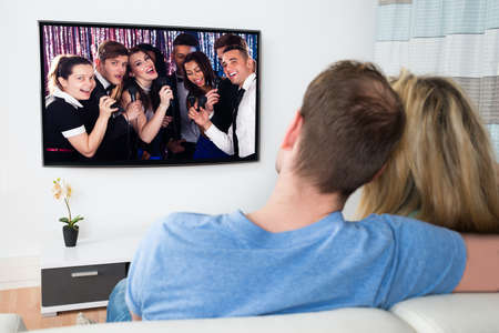 television show: Couple Watching Movie On Television At Home Stock Photo