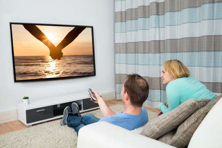 Couple Together Watching Film On Television At Home