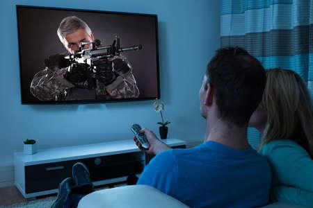 pareja viendo television: Vista posterior de observación de los pares de Cine En Sala