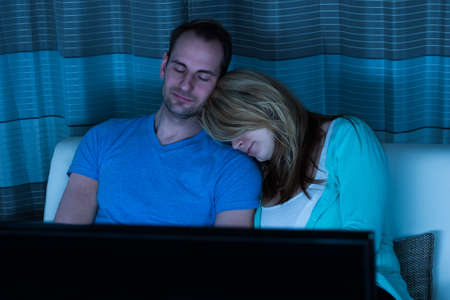 somnolence: Couple Sleeping On Sofa In Front Of Television At Home