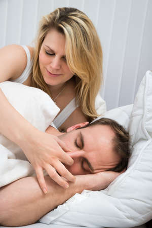 snoring: Happy Woman Is Holding Husbands Nose In Bedroom