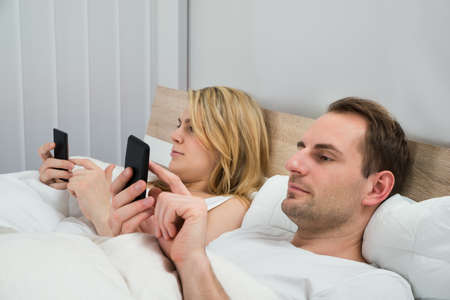 in: Couple Lying In A Bed Using Mobile Phones