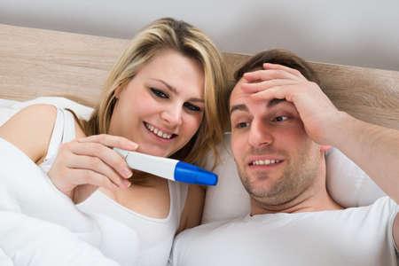 cheerful woman: Pares que miran una prueba de embarazo positiva en el dormitorio