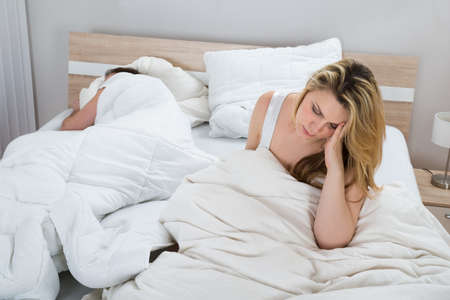 nude woman sitting: Unhappy Woman With Blanket On Bed While Man Sleeping In Bedroom