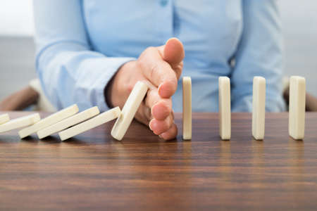 chain reaction: Close-up Of Businesswoman Stopping The Effect Of Domino With Hand At Desk