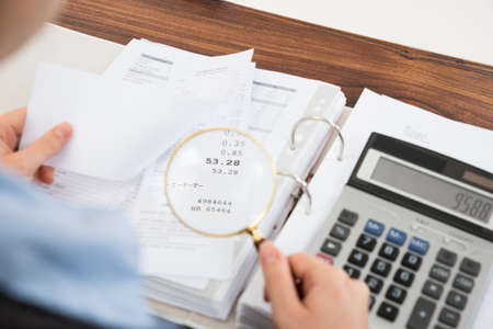 Close-up Of Businessperson Examining Receipts With Magnifying Glass