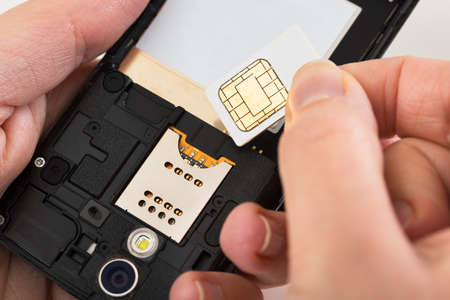 micro drive: Close-up Of Person Hand Inserting A Sim Card Into Mobile Phone Stock Photo