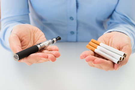 Close-up Of Businessperson Holding Electronic Cigarette In Hand