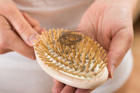 comb hair: Close-up Of Person Hand Holding Comb With Loss Hair