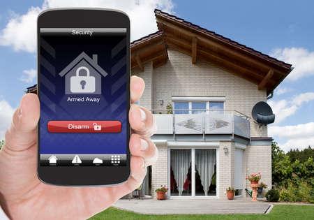 system: Close-up Osoba strony posiadania telefonu komórkowego z rozbrajającą Security System Zdjęcie Seryjne
