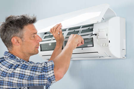 setup man: Portrait Of Mid-adult Male Technician Repairing Air Conditioner Stock Photo