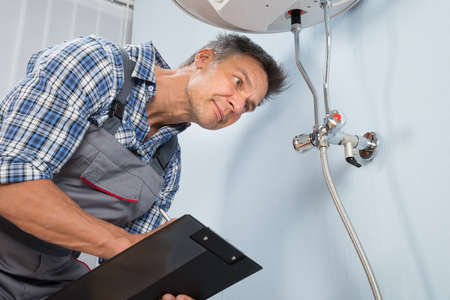 Portrait Of Male Plumber Holding Clipboard Looking At Electric ...